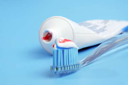 toothbrush with tricolor toothpaste on it and white toothpaste tube on blue background