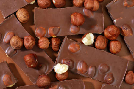 top view on pieces of milk chocolate and hazel nuts