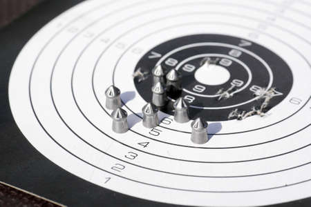 closeup of paper shooting target with bullet holes and airgun pellets