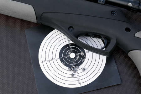 top view of air gun, paper shooting target with bullet holes and airgun pellets Stock fotó - 155844420