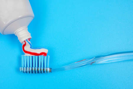 closeup of squeezing toothpaste on toothbrush on blue background with copy space