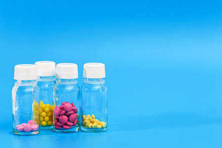 various pills in glass bottles on blue background with copy space