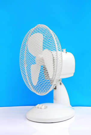 white table oscillating fan on blue background