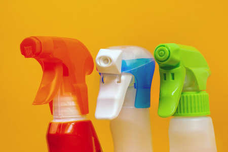 Close up of three different spray bottles on yellow