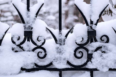 fragment of wrought metal black fence covered with snow after snowfall