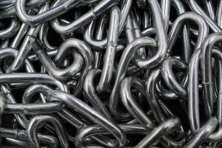 macro of metal chain links in heap, abstract background