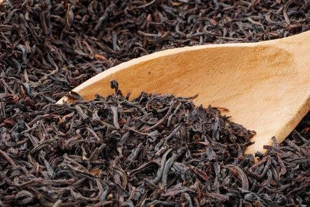 macro  of black loose long leaf tea with wooden spoon Stock fotó