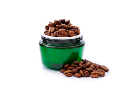 Green face cream jar with coffee beans in it on isolated on white background. Natural herbal cosmetics concept,