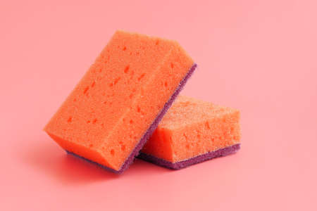 Orange sponges on red background. Dishwashing and household cleaning tools. Tool for having dish and kitchenware clean.