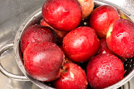 Top view on washed fresh ripe nectarines in steel colander. Water drops on washed nectarines.