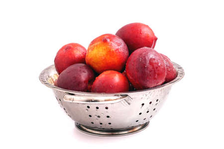 Fresh ripe nectarines in steel colander isolated on white background. Water drops on washed nectarines. Stock fotó