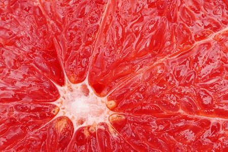 Macro of ripe grapefruit pulp. Slice of red grapefruit close up. Grapefruit fruit texture wallpaper background Stock fotó