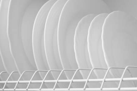 Clean white plates on dish drainer drying after washing