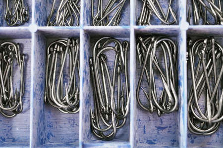 Top view of tackle box with fishing hooks. Fishing hooks in box sections. Macro of fishhooks.