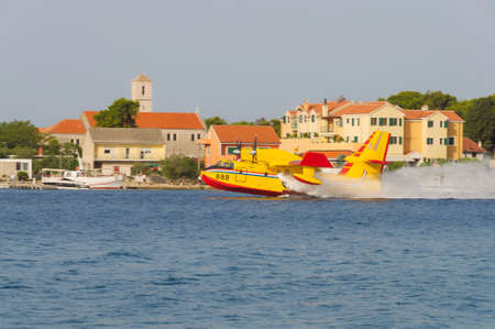 bombardier: SIBENIK, CROATIA, August 6 2012 - Bombardier 415 Superscooper (Canadair cl-415) scooping water in tight channel near Sibenik