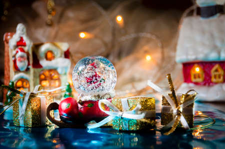 Christmas still life with Santas snowball and lights in the background, selective focus