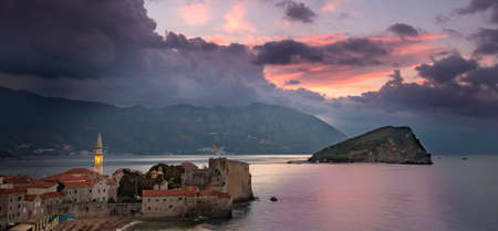 old towns: Sunrise over Budva old town with lit tower of Sv. Ivan church, old towns citadel and island Sv. Nikola to the right. Picturesque mountains and coast in background