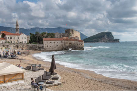Budva, Montenegro - October 21 2016: tourists on Richards head beach watching a storm surge hitting against the citadel walls and flooding the beach. The beach is famous after Richard Widmark, who shot a movie in 1963 in the exact same spot located in ol Editorial