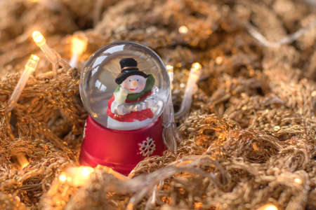 snowdome: Snowman in snowglobesnowball on golden, glittery runes with led lights illuminating the scene. Christmas home decoration example. Stock Photo