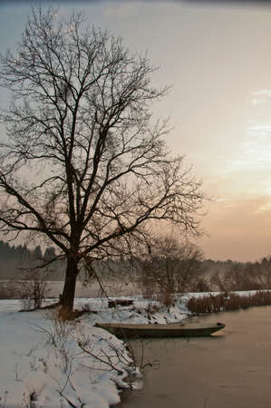 adds: A boat encased in ice on a lake in winter. Above the boat is a big oak tree with a bench. The fog at sunset adds to the mistery of the scene.