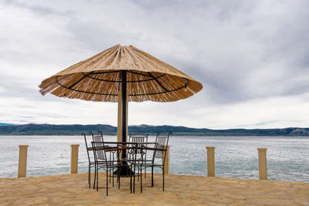 Terrace at the sea with chairs, table and straw parasol, sea and an island in the background