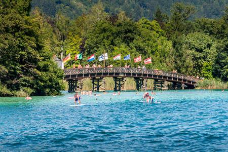 Portschach, Oostenrijk - Augustus 14 2016: Internationale vlaggen die over het reiling van de houten brug vliegen die van Portschach tot Blumeninsel leiden (bloemeiland) terwijl de zwemmers van het water op een hete de zomerdag genieten. Stockfoto