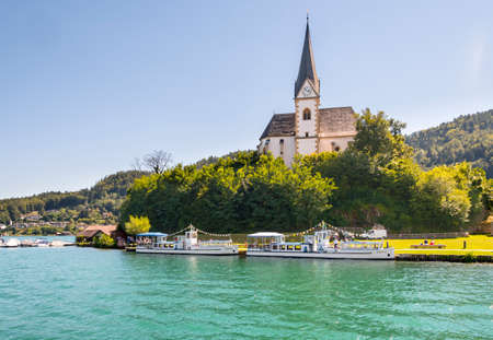 primus: Maria Worth, Austria - August 14 2016: Vintage tourist boats at the church of Maria Worth waiting for passengers. Saints Primus and Felician Church in the background is popular pilgrimage site.