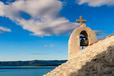 Small stone chappel in the Mediterranean, island of Brac, Croatia  morning daylight, Hvar in background
