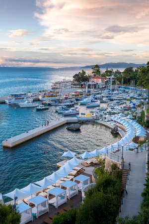 Opatija, Croatia - September 6 2016: Crowded harbor in the morning after heavy storms and deserted hotel beach in forground.