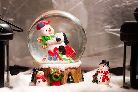 snowdome: Snowman in snowdome, Christmas decoration at home, Happy New Year 2017, closeup, fake snow Stock Photo