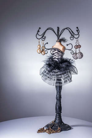Black jewelery display stand  hanger in form of a womans bust in black and white dress with metallic arms as holders
