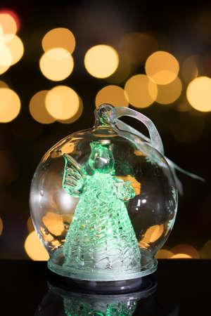 Illuminated angel figure in glass bulb, soft boke christmas ligh Stock Photo