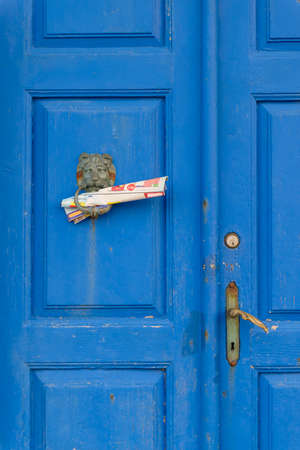 A vintage blue wooden double door with bronze knocker and newspapers
