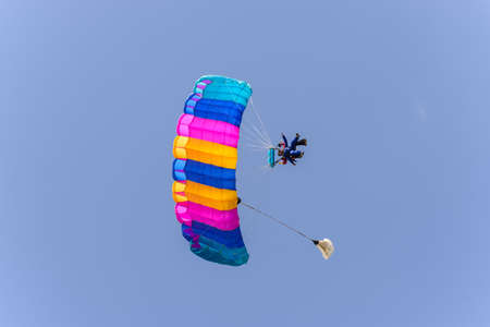 Skydiver tandem with parachute open landing