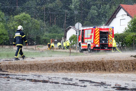 Red fire brigade engine,firefighting truck and firefighters rush to rescue when floods hit village in Europe after heavy rain, severe weather, rescue services