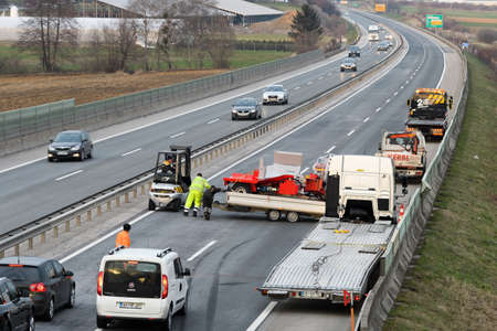Slovenska Bistrica - March 23, 2018: Tow truck workers cleaning wreckage after traffic accident on highway after a small truck lost control and its trailer crashed into the security fence