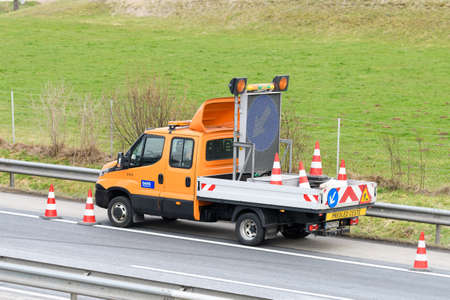 Slovenska Bistrica - March 23, 2018: Tow truck workers cleaning wreckage after traffic accident on highway after a small truck lost control and its trailer crashed into the security fence Editorial