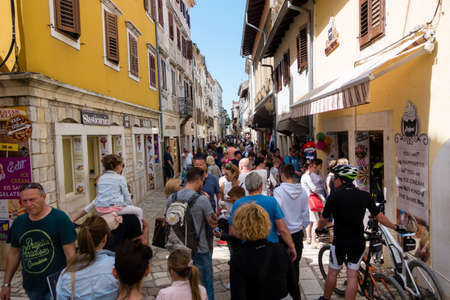 Porec, Croatia - April 30, 2018 Tourists walking through the main street of medieval town of Porec, Croatia. Porec is a popular tourist destination in Istria. Editorial