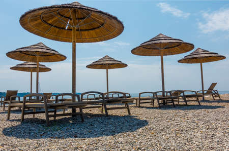 Beach with beach chairs in morning light on the beach of a Croatian seaside holiday resort in Porec, Istria, no people