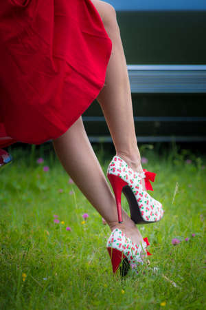 Pin Up Girl Style, young woman in red dress with long legs, wearing red high heels stilettos with cherries Stok Fotoğraf