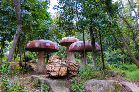 Gigantic red wooden mushrooms on a playground in woods
