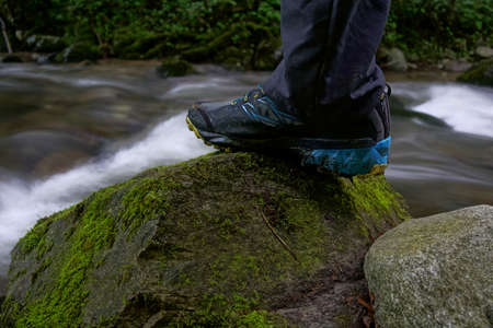 Close up of trekking, hiking shoes on hiker outdoors walking crossing river, creek in mountains