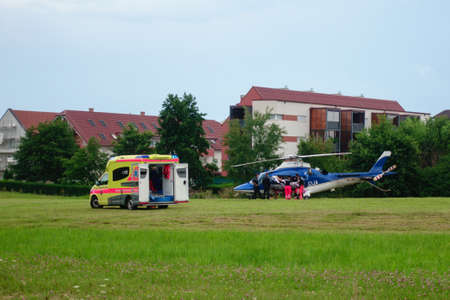 Slovenska Bistrica, July 21 2018: Paramedics hand over patient to Police helicopter for emergency aerial transport to hospital. Ambulance car with flashing lights. Live news.