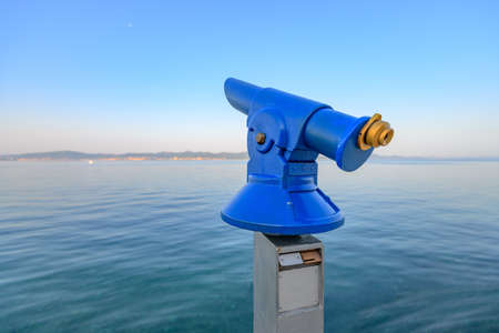 Blue public coin operated telescope, sea and island in background, located on waterfron early in the morning