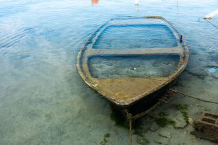 Small sunken boat in harbor submerged in shallow water and moored Stock Photo