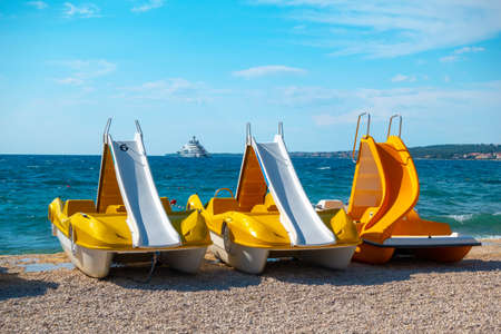 Colorful pedal boats, pedolinos on beach, yellow color, boat with slide, sea in the background Imagens