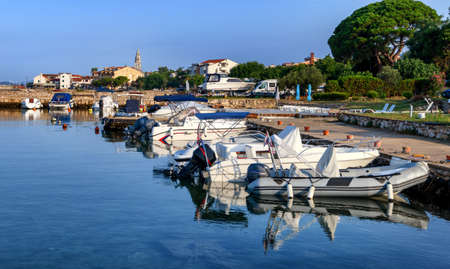 Turanj village harbor and waterfront view, Dalmatia, Croatia, small motor boats and sailing boats moored in harbor, sky reflecting in water, early morning