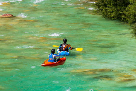 A couple kayaking in emerald, turquoise mountain river, wearing wetsuits and avoiding roks and boulders in the streaming water, facing away, red and blue kayak