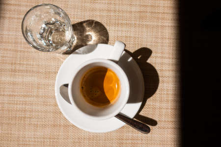Caffe corretto, traditional Italian beverage with espresso and a shot of liquor, usually grappa, top view on beige background and dark frame to right, copyspace Foto de archivo