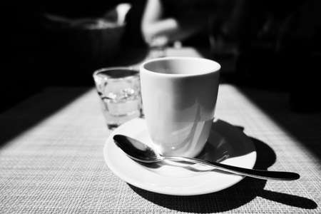 Caffe corretto, traditional Italian beverage with espresso and a shot of liquor, usually grappa, copyspace, black and white, dramatic lightning